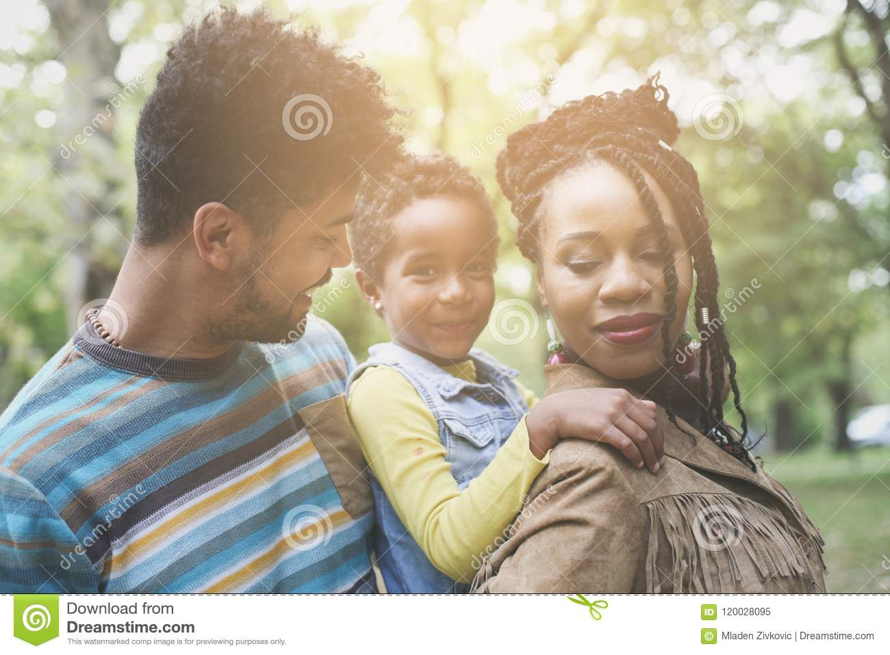 Portrait of young African American family in park.