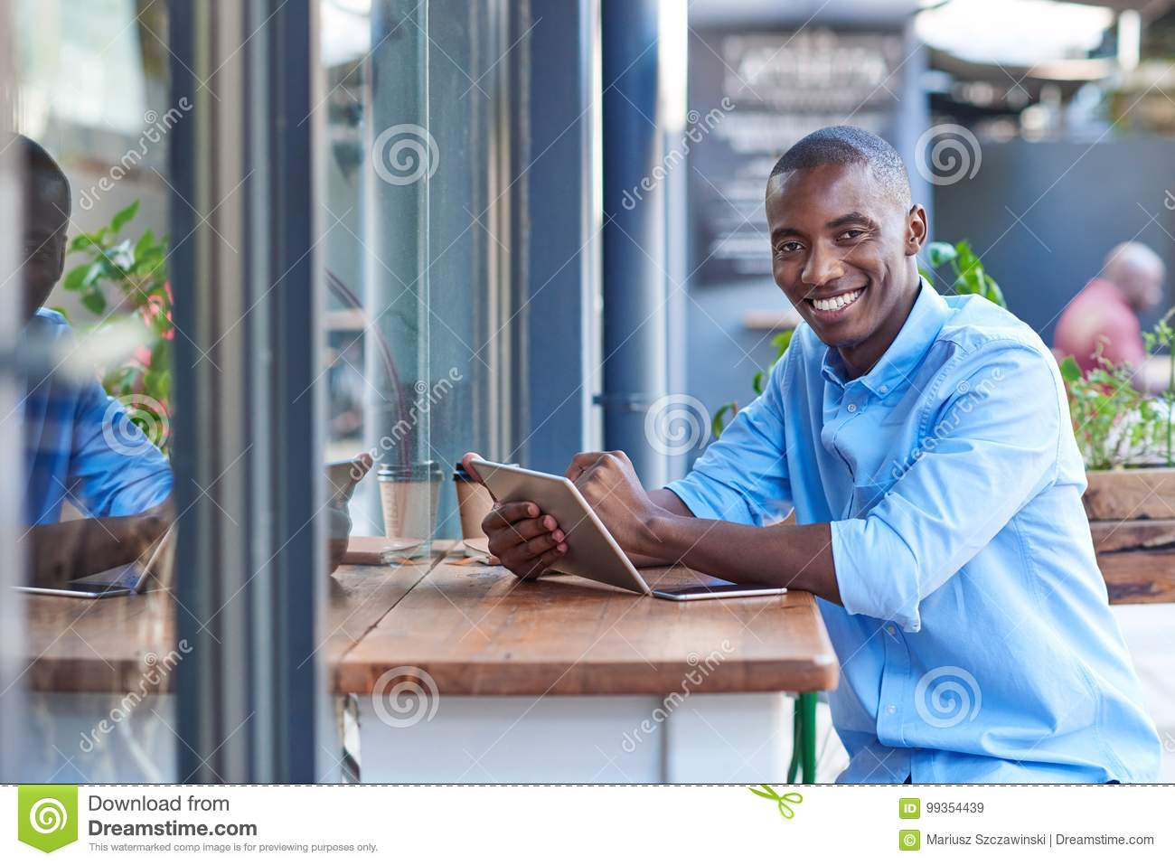 Smiling African man working online at a sidewalk cafe counter