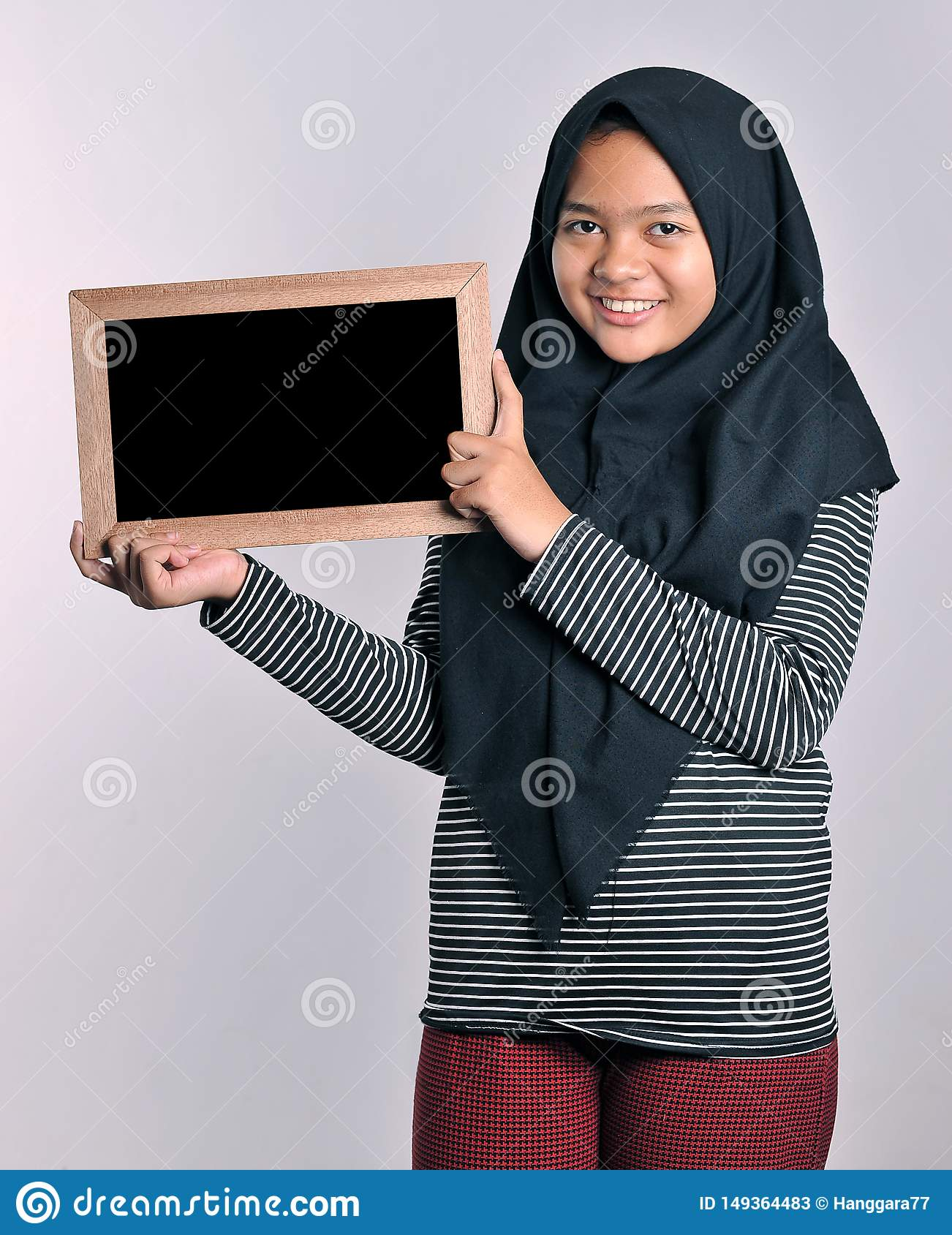 Portrait of young asian woman in islamic headscarf holding chalkboard. Smiling asian woman wearing islamic headscarf holding