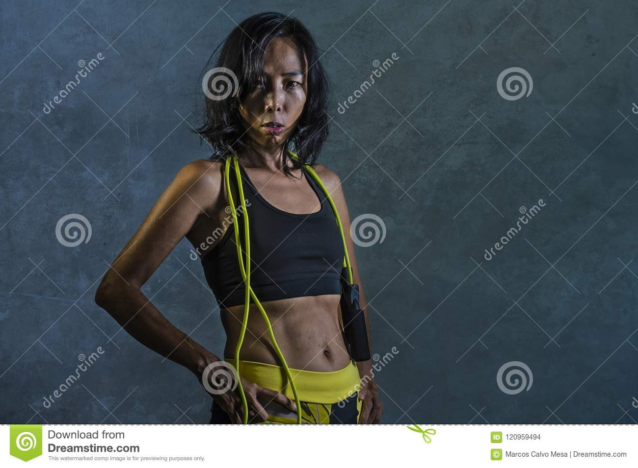 a90fa3d3c9c1b Portrait of young athletic and fit Asian Korean woman in fitness top  holding skipping rope posing cool in bad girl defiant attitude isolated on  dark ...