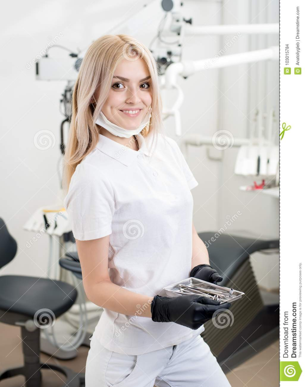 Portrait of young attractive female dentist holding dental tool at the modern dental office