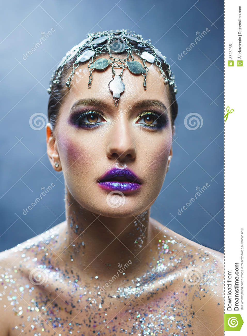 Portrait of a young attractive girl with a creative make-up and decorations.