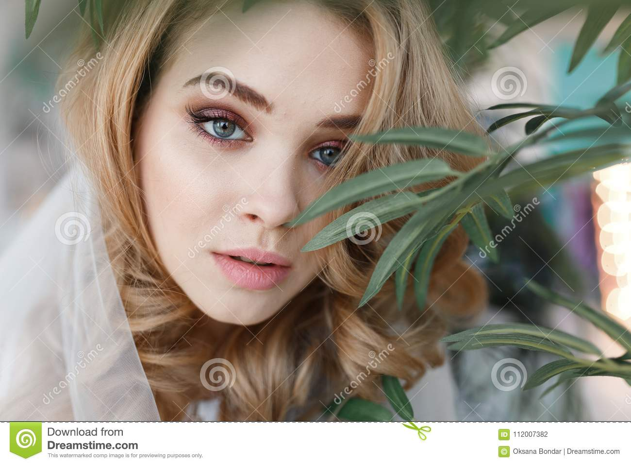 8ff725e9a619a Portrait of young attractive girl with perfect skin among green leaves.  Close-up horizontal