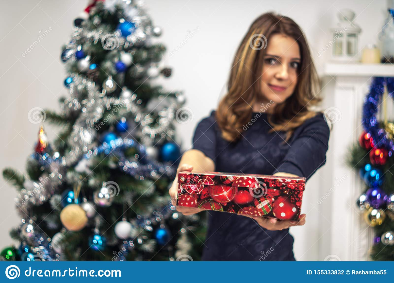 Portrait of a young, attractive and photogenic woman smiling as she holds up a box that she received for a gift. She is standing