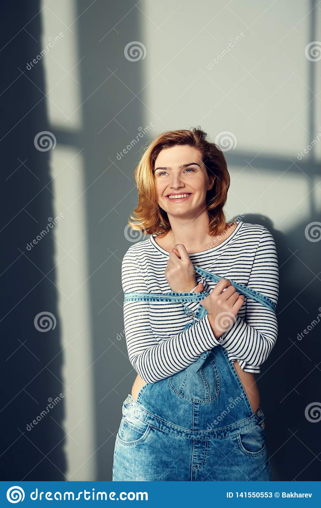 Portrait of a young attractive stylish emotional woman in jeans overalls