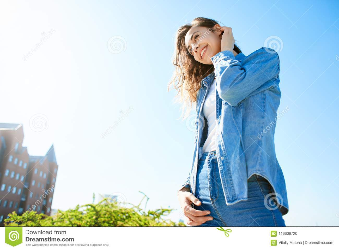 Portrait Of A Young Attractive Woman On The Blue Sky