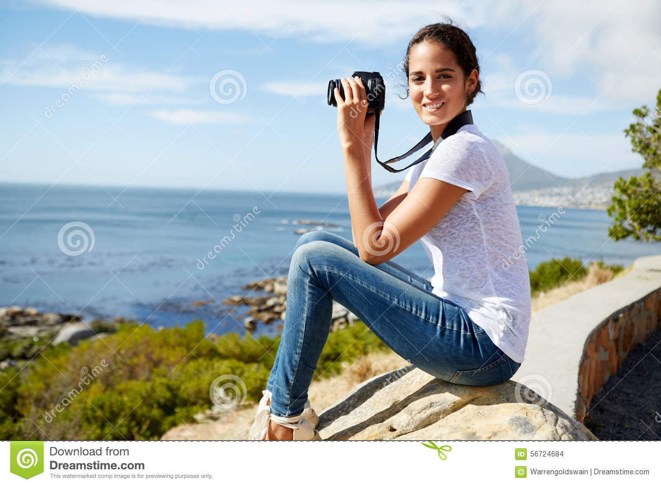 Portrait of a young, attractive woman sitting on a rock with dig