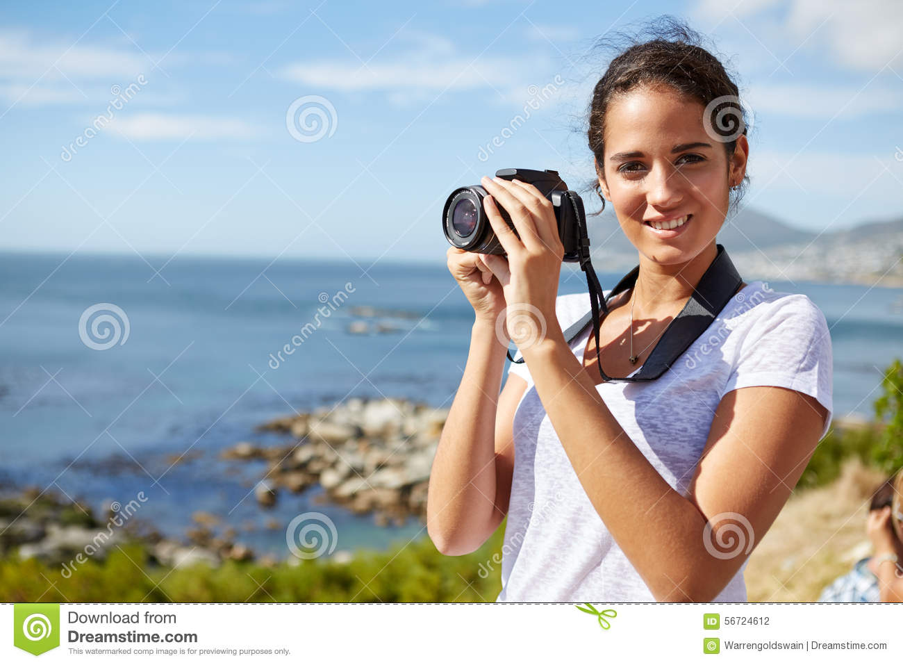 Portrait of a young, attractive woman standing near the ocean wi