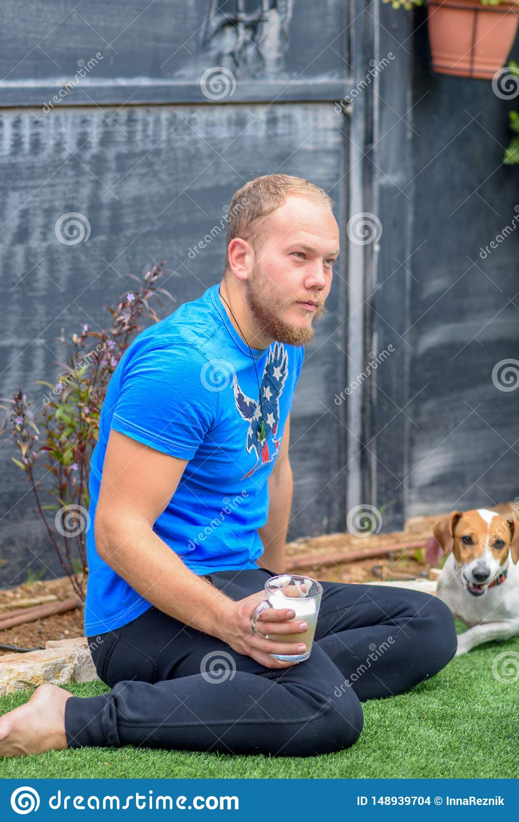 Portrait Of A Young Bearded Man and Dog Outdoor.
