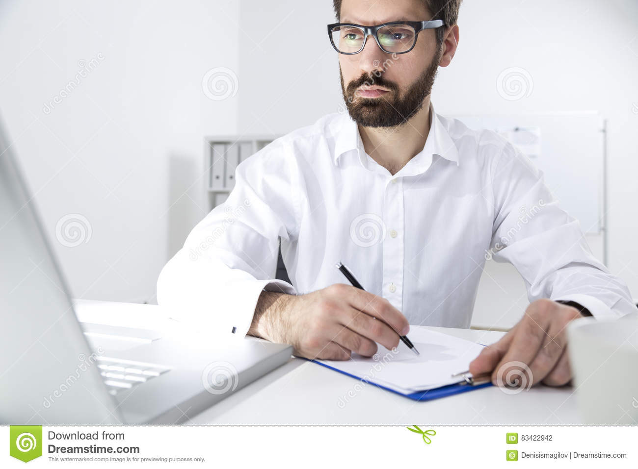Portrait of a young bearded man taking notes