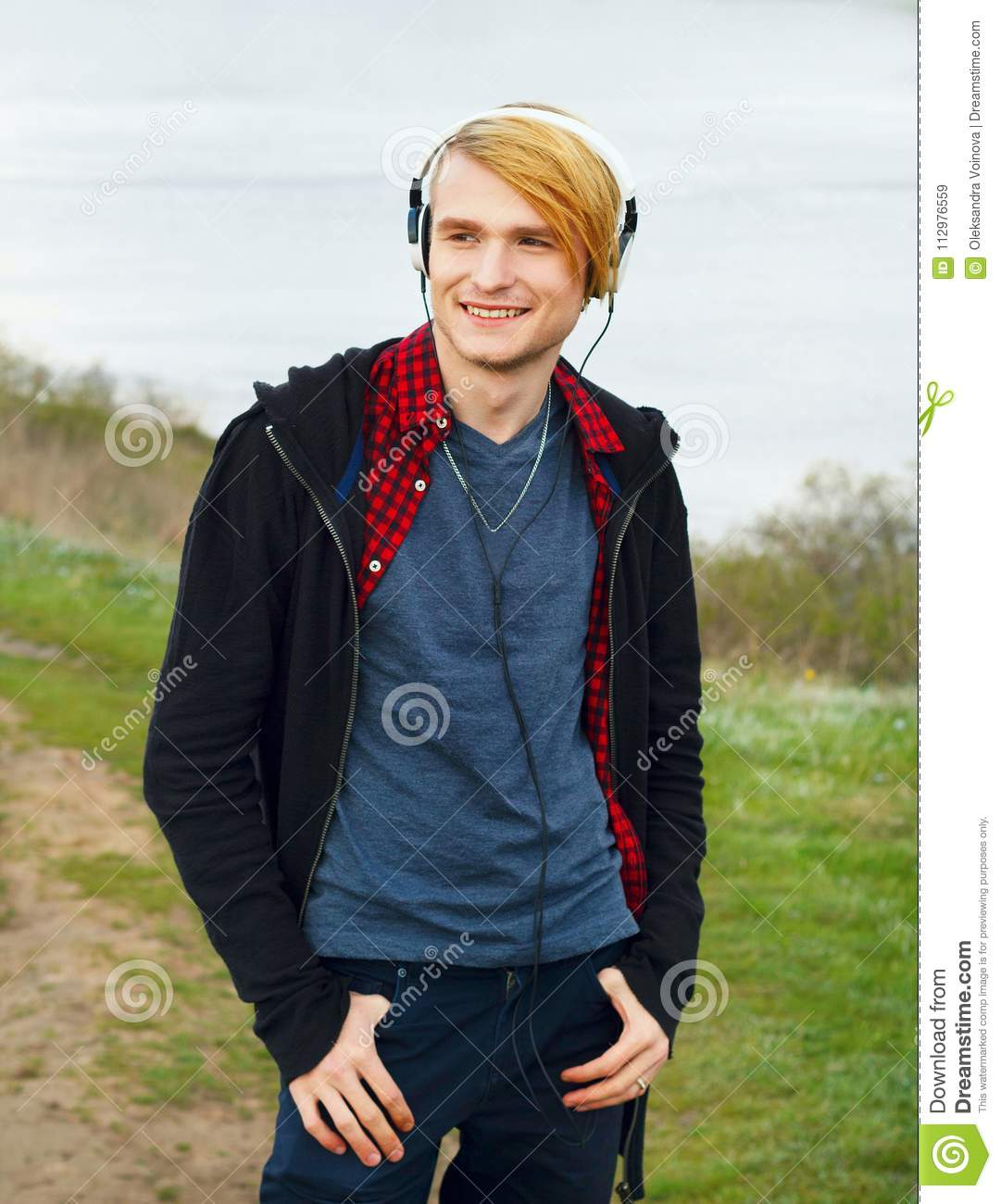 Portrait of young beautiful blond hipster man with headphones st