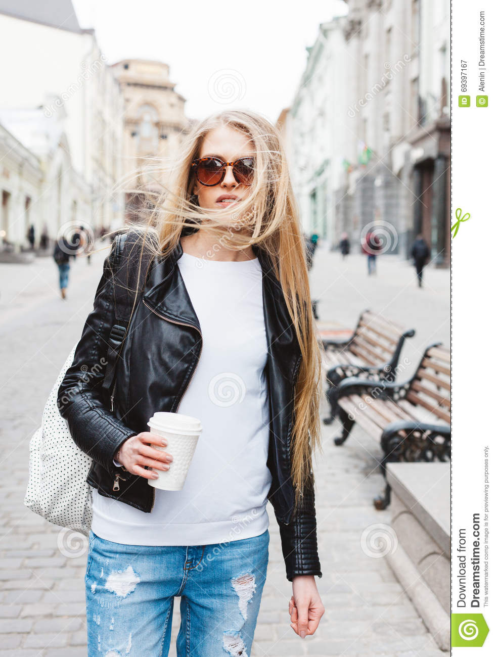 Portrait of a young beautiful blonde girl with sunglasses walking on the streets of Europe with coffee. The wind blowing her hairO