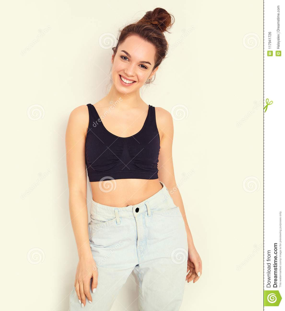 12e8de3722abe Portrait of young beautiful brunette woman girl model with nude makeup in  summer T-shirt top and jeans hipster clothes posing near wall. Going crazy