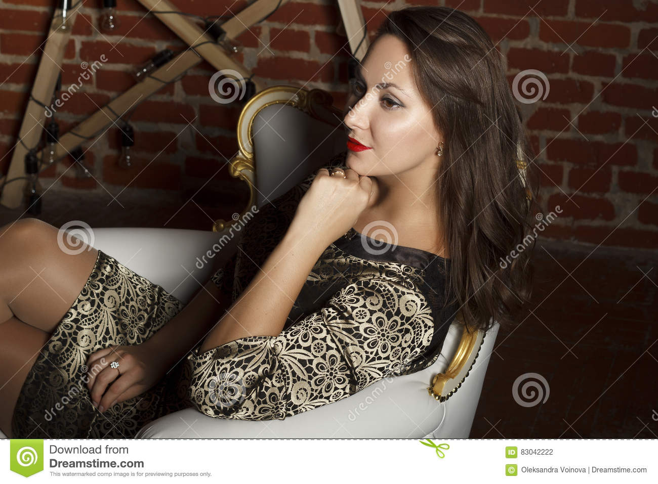 Portrait of young beautiful brunette woman sitting in chair as a