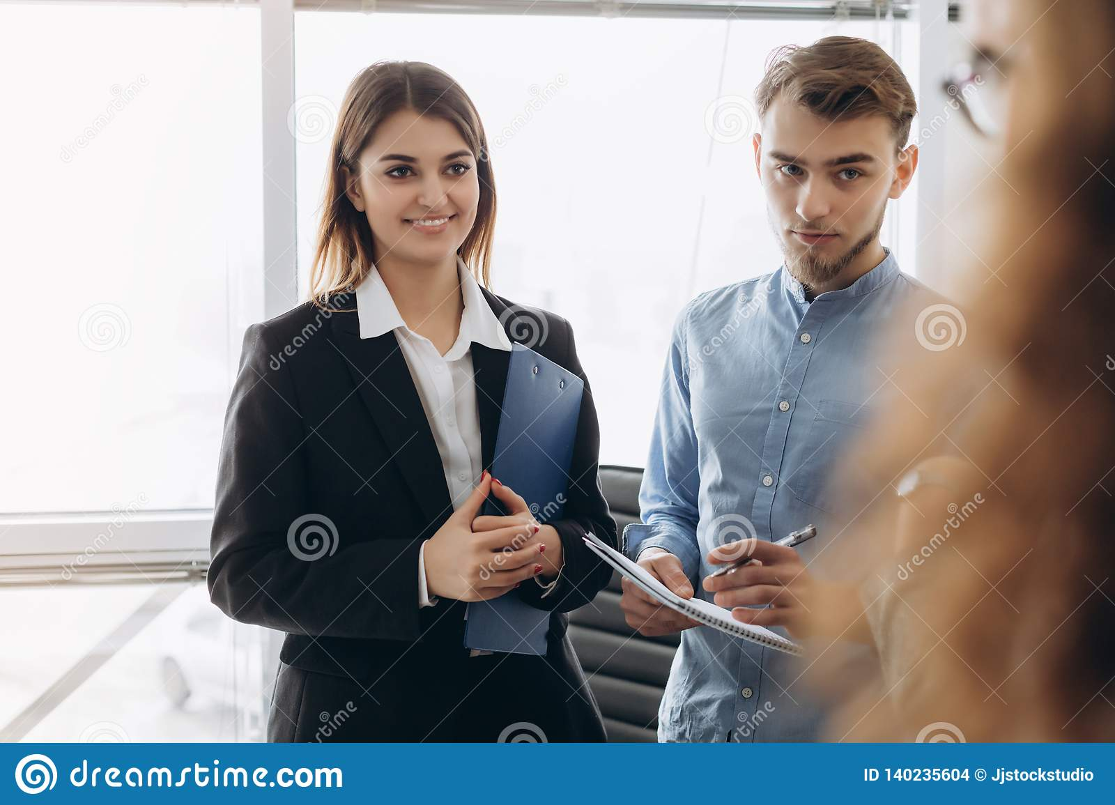 Portrait of young beautiful business woman in the office speaking with workers