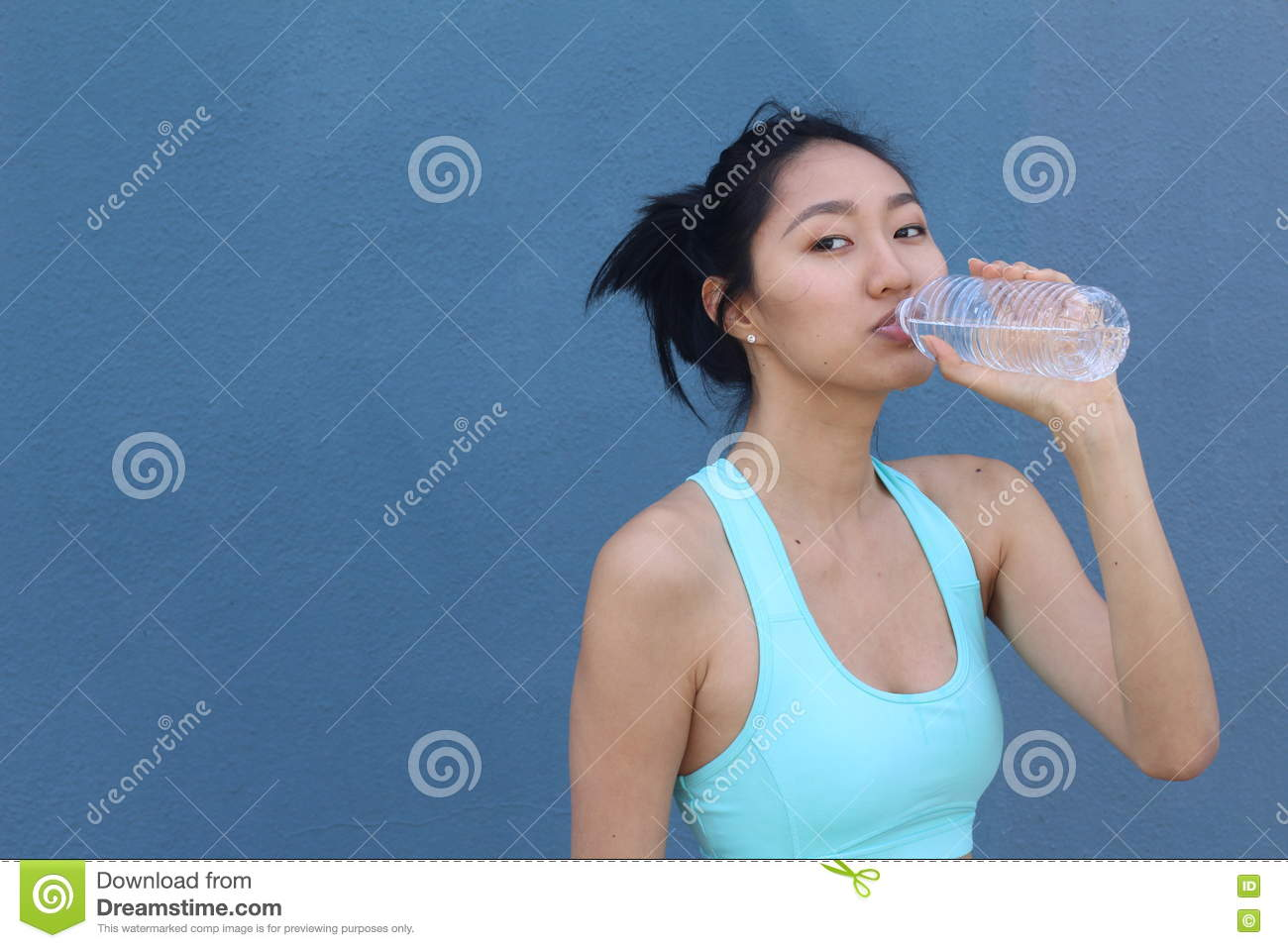 Portrait of young beautiful dark-haired Asian woman wearing blue t-shirt drinking water at summer blue sky