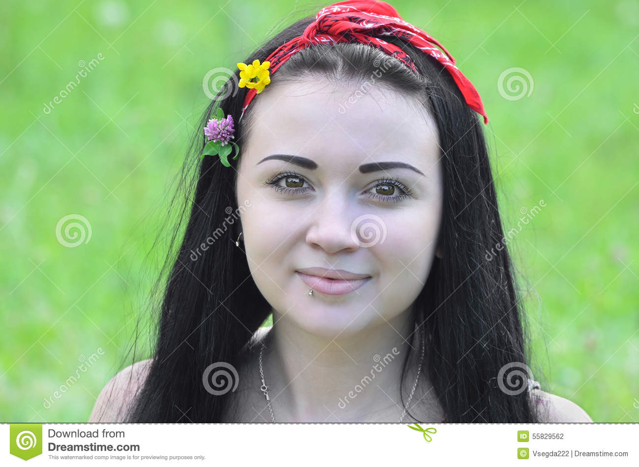 Portrait of a young, beautiful girl, brunette with flowers in her hair and scarf