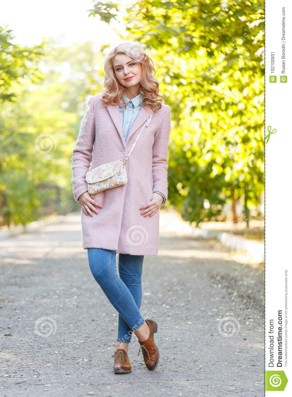 Portrait of a young beautiful girl in a pink coat. In the park.