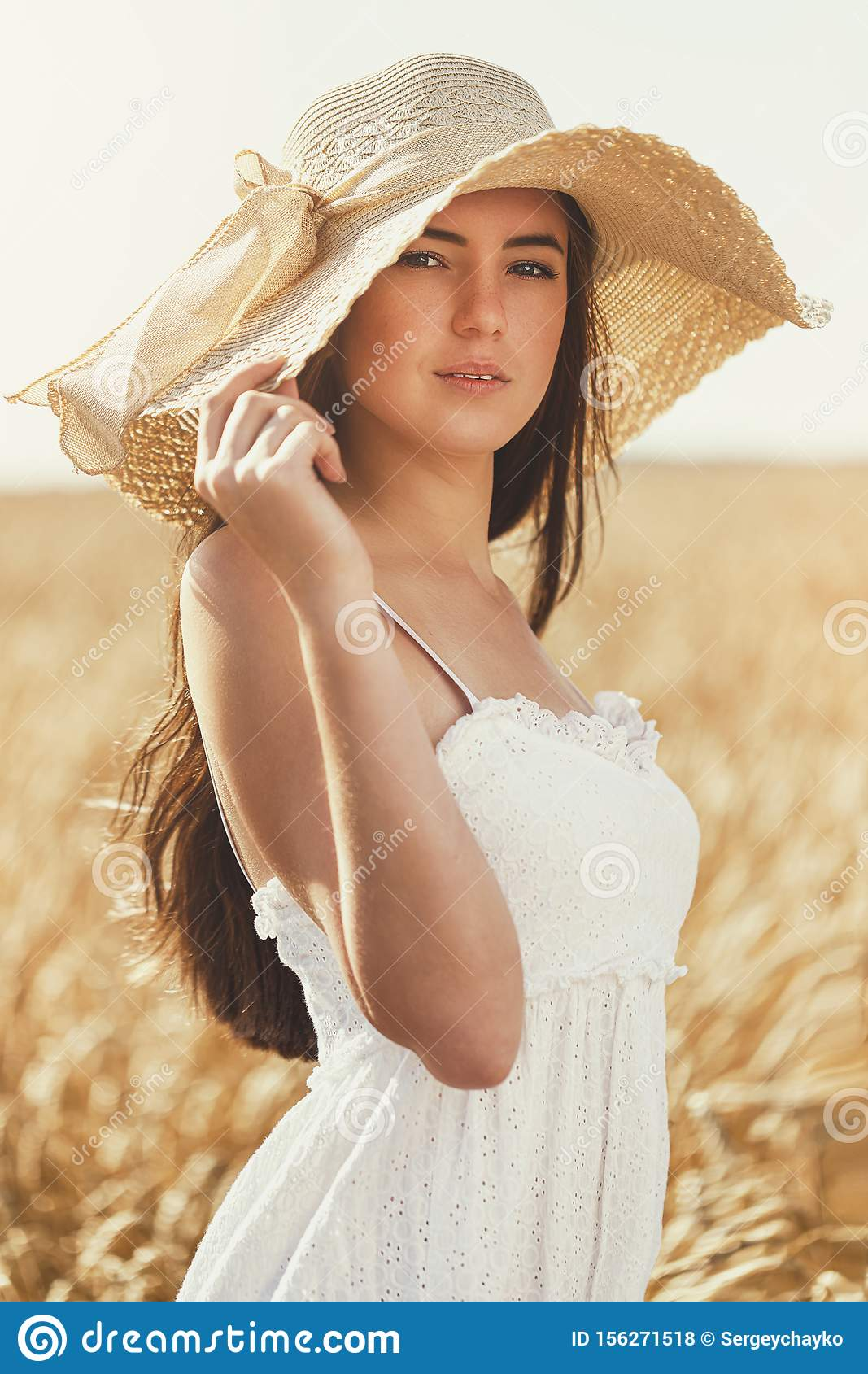 Portrait of a young beautiful girl in a white dress in the sun