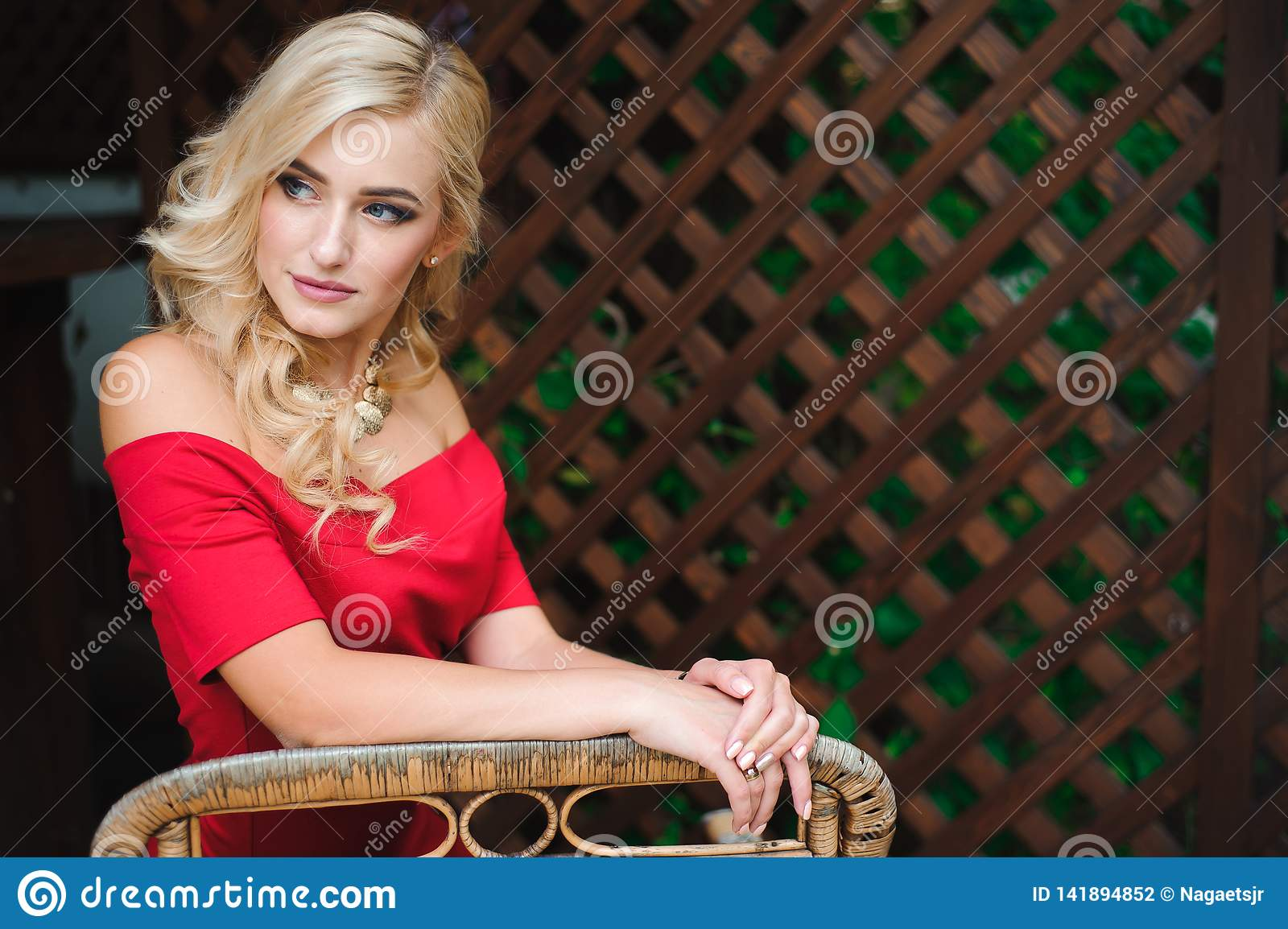 Portrait of young beautiful tanned blonde woman in red evening dress sitting outdoor in street cafe alone