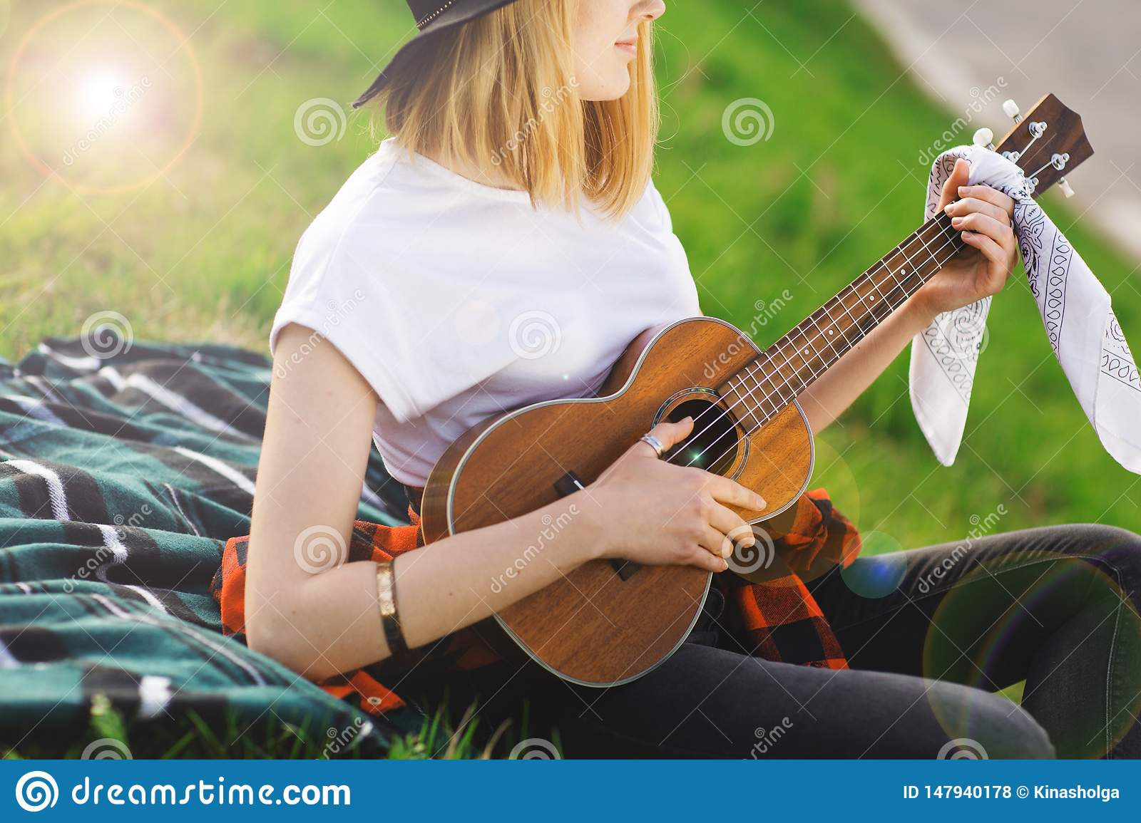 Portrait of a young beautiful woman in a black hat. Girl sitting on the grass and playing guitar