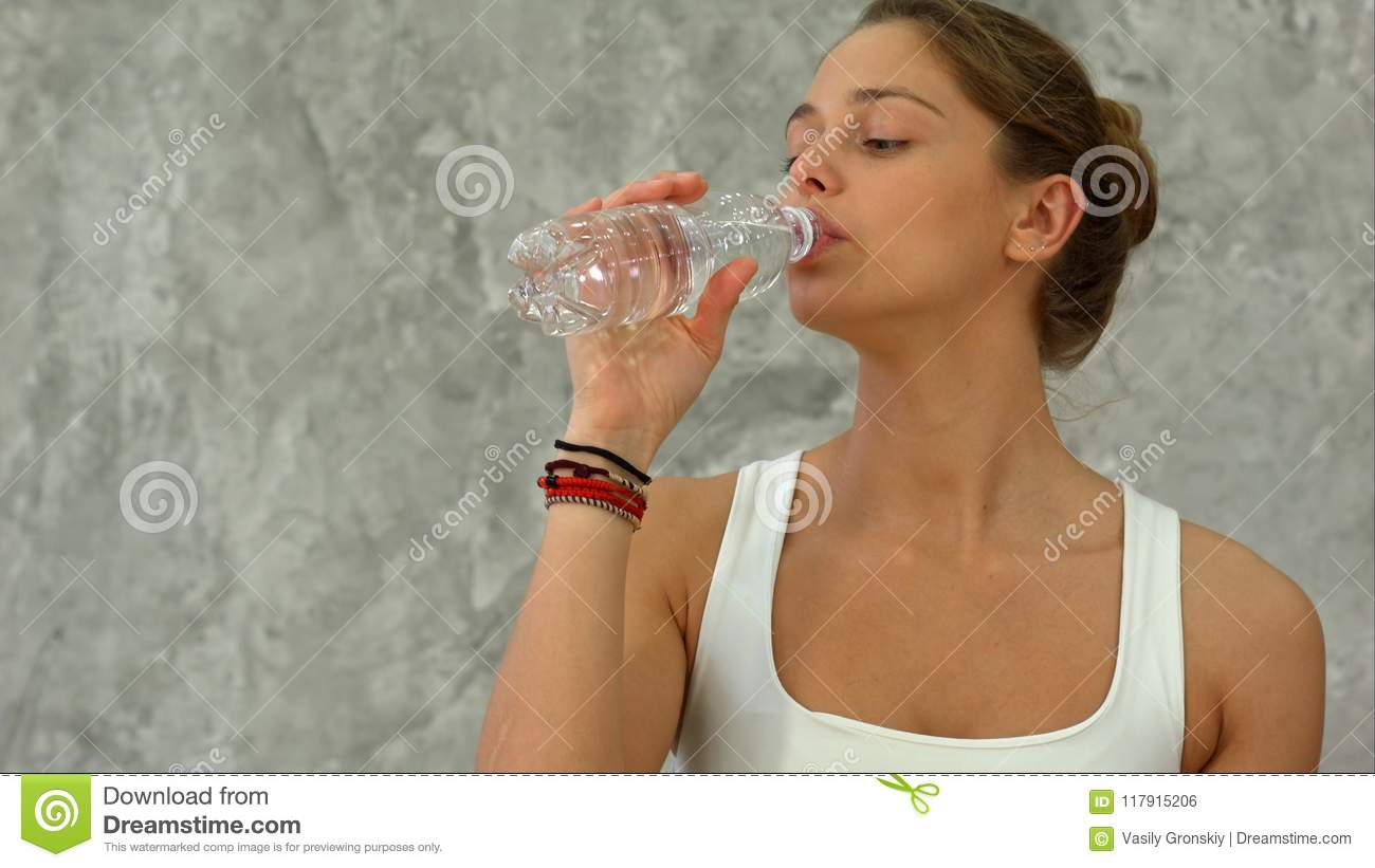 Portrait of young beautiful woman drinking water after yoga class