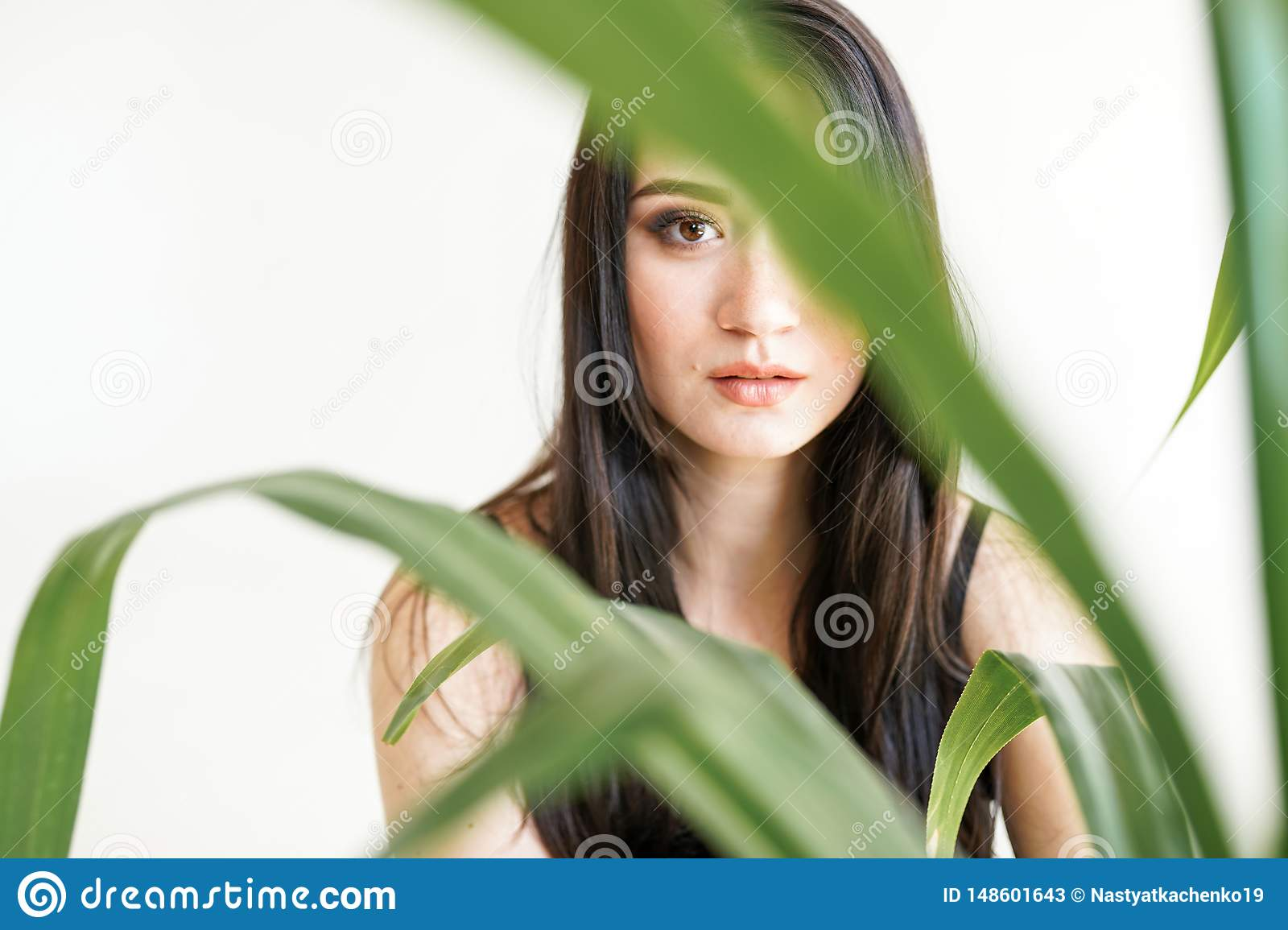 Portrait of a young beautiful woman with greenery . Summer fashion photo. Skin care concept, beauty spa, bio product