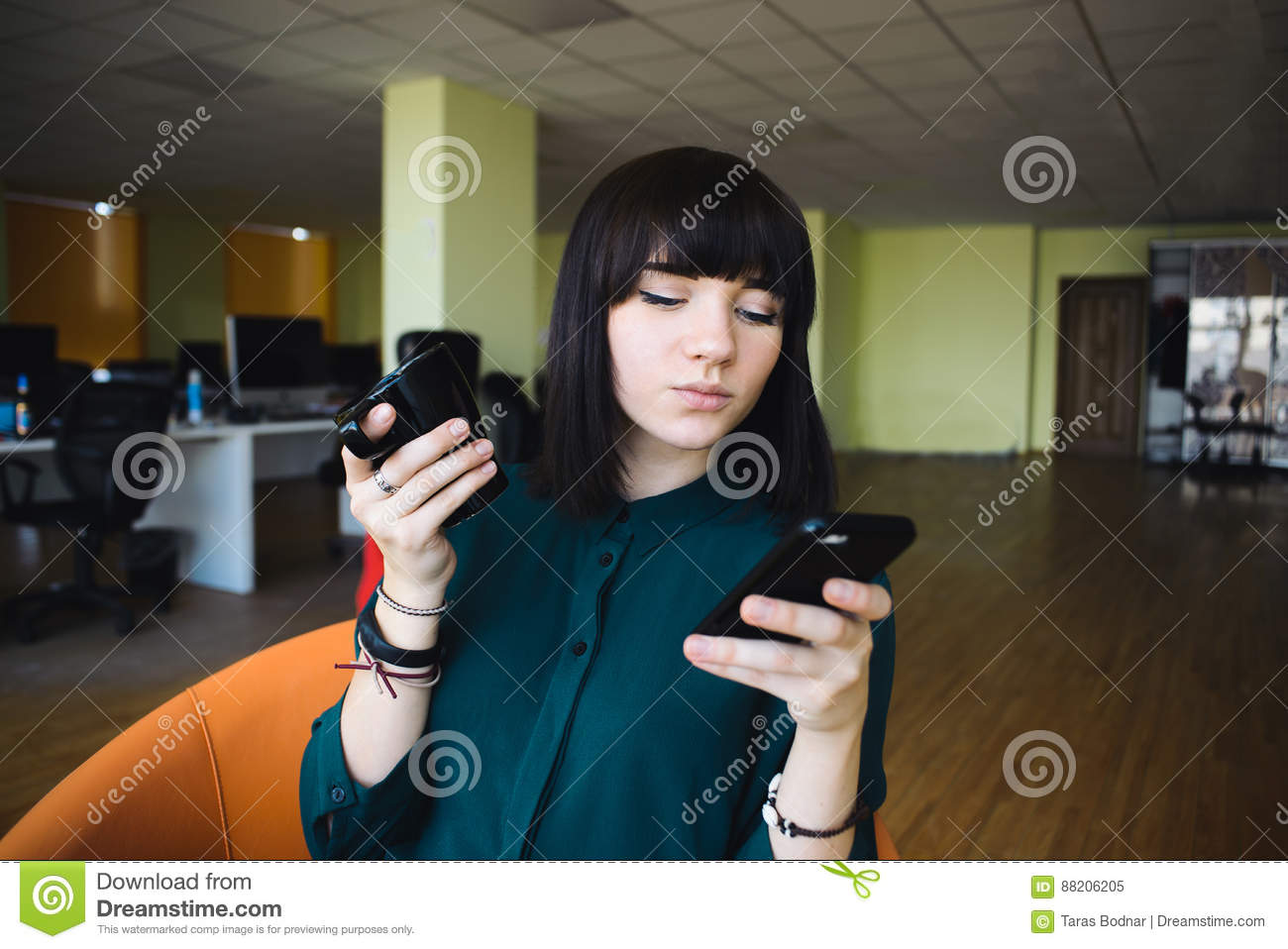 Portrait of a young, beautiful woman office worker who uses a mobile phone and holding a cup of drink.