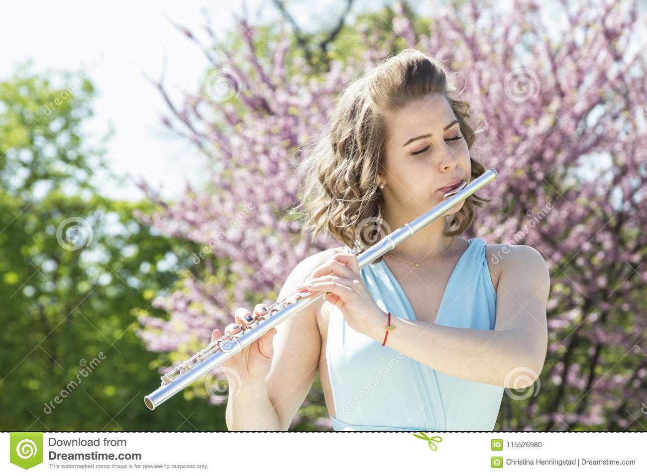 Portrait Of Young Beautiful Woman Playing Flute  Stock Photo - Image