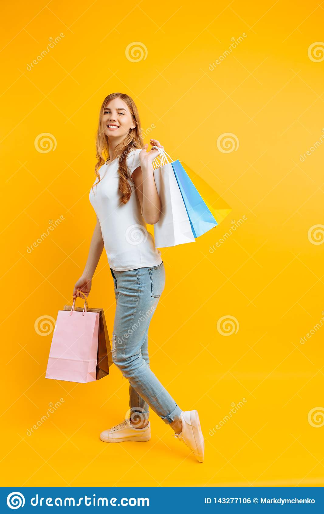 Portrait of a young beautiful woman in a white T-shirt, with multi-colored bags, on a yellow background