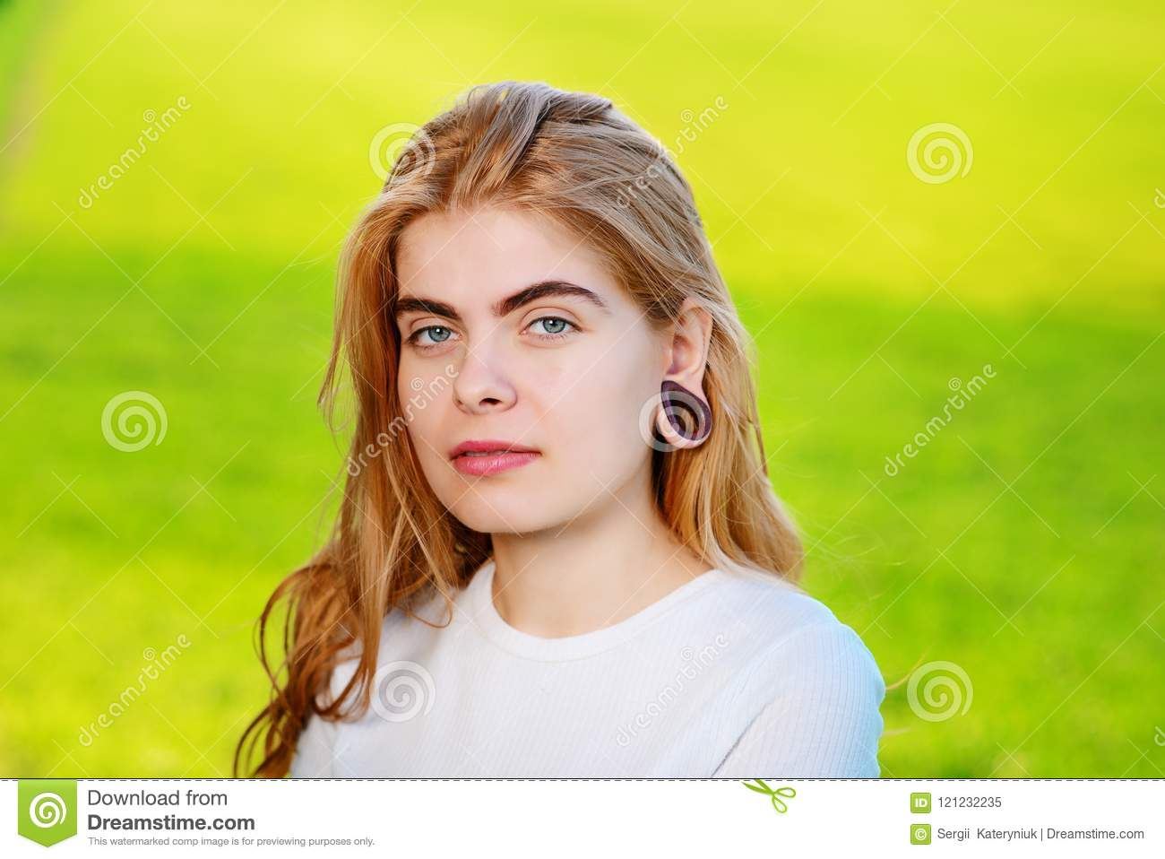 Portrait of a young beautiful woman with wooden tunnels in her e