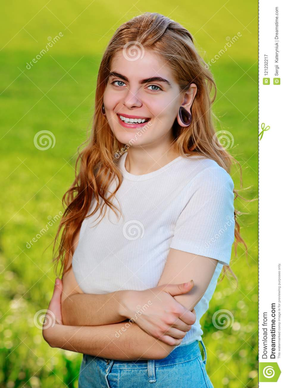 Portrait of a young beautiful woman with wooden tunnels in her ears