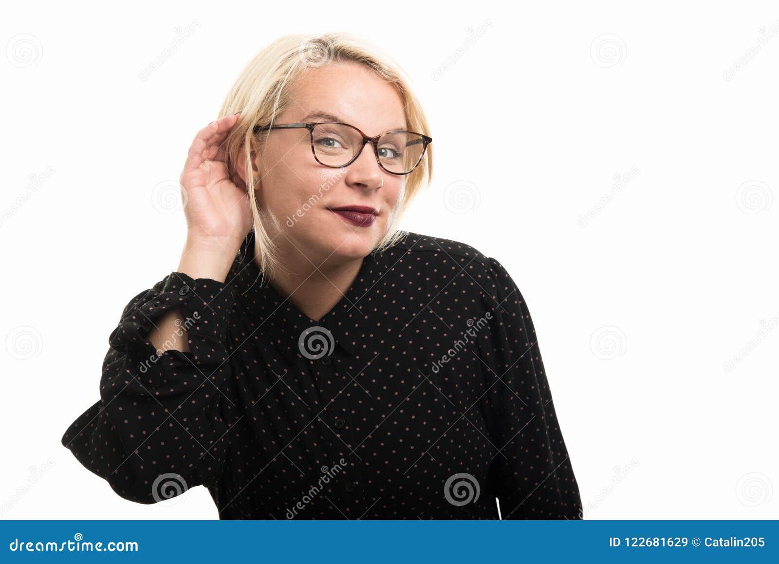 Blonde female teacher wearing glasses showing can`t hear gesture