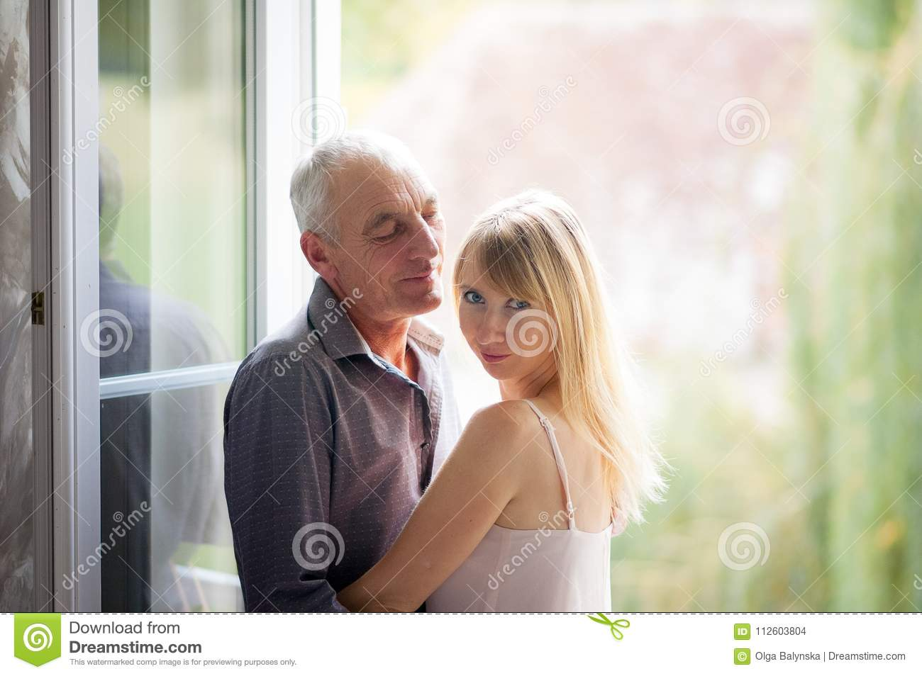 Portrait of Young Blonde-haired Woman in Short Summer Dress Standing near the Window with Her Senior Husband. Couple