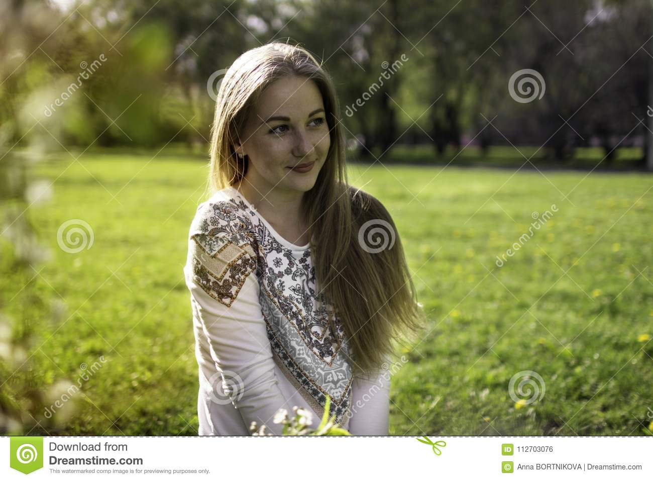 portrait of a young blonde woman in a spring forest and in sunlight