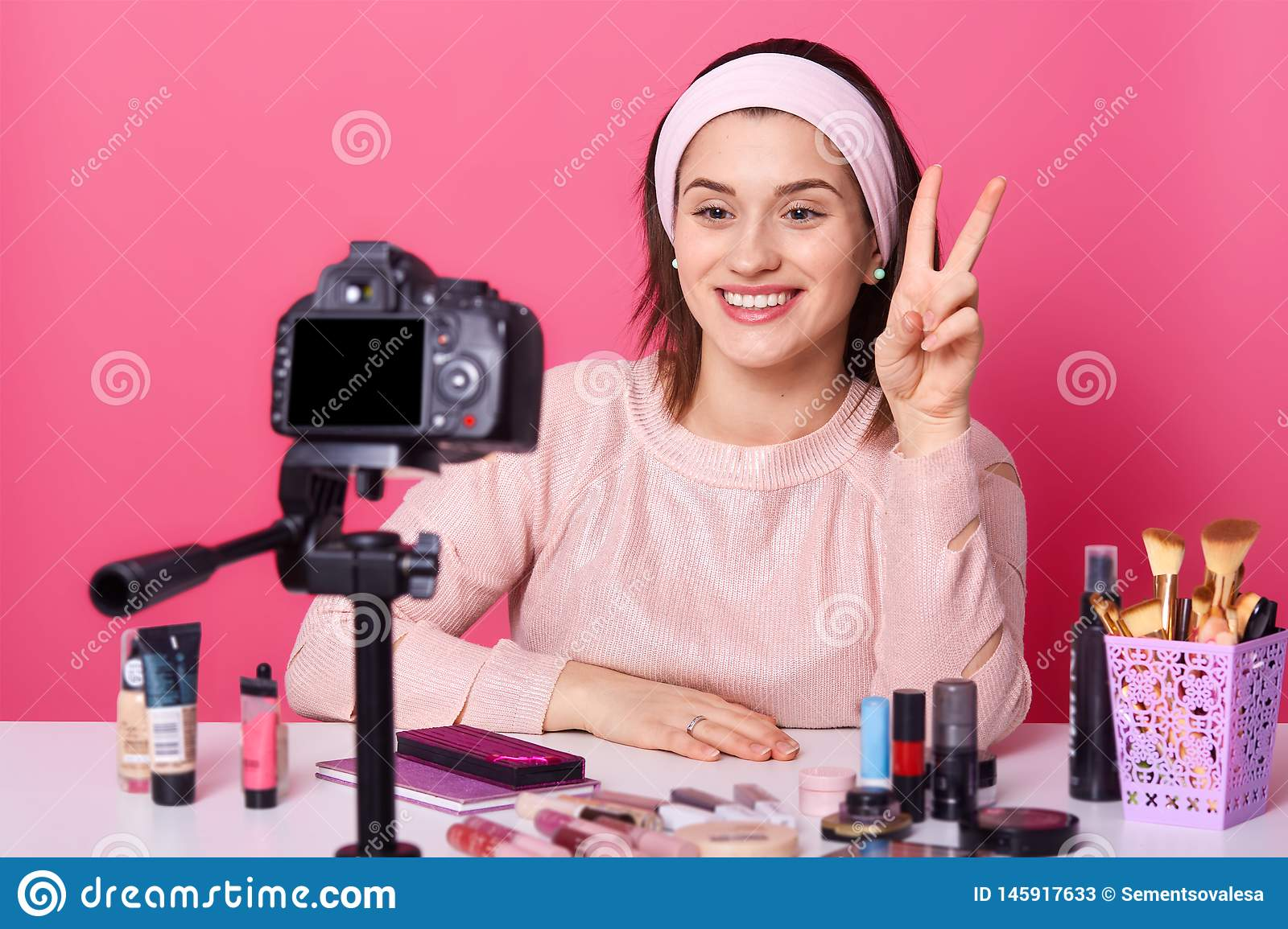 Portrait of young brunette blogger taking video via digital camera and showing peace sign. Cheerful model posing in studio on pink