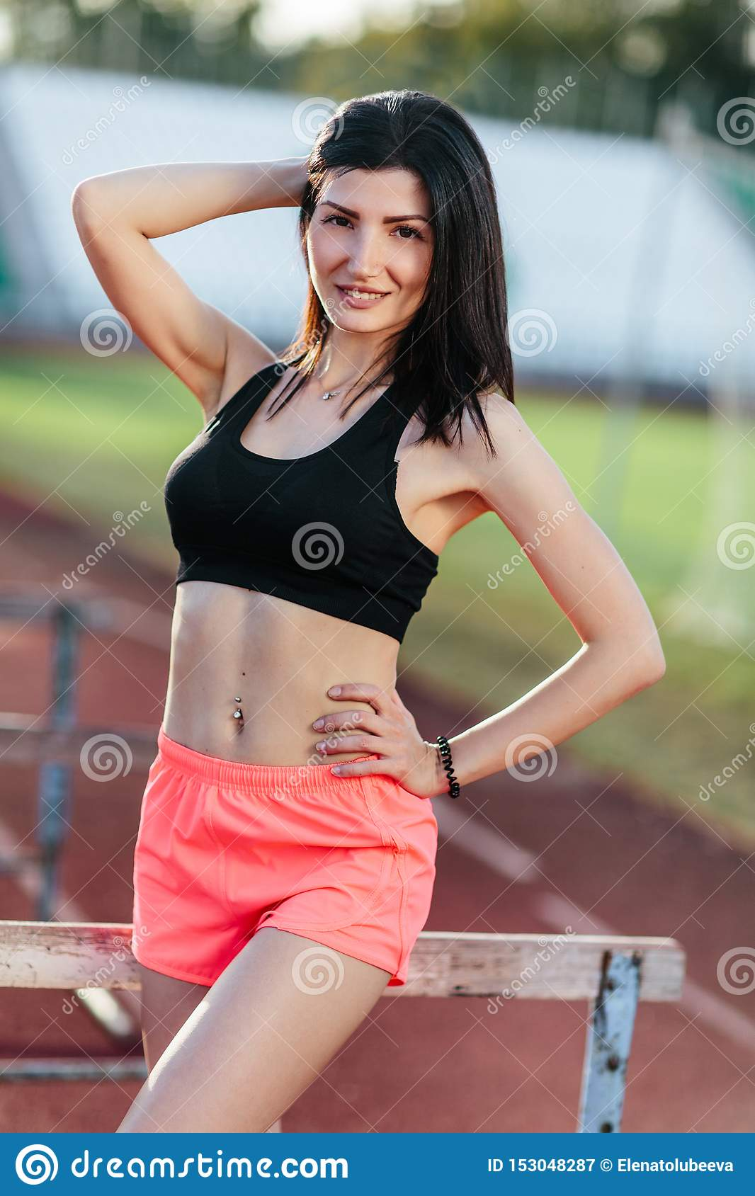 Portrait of young brunette woman athlete on stadium sporty lifestyle standing on track posing near the barriers running jumping to