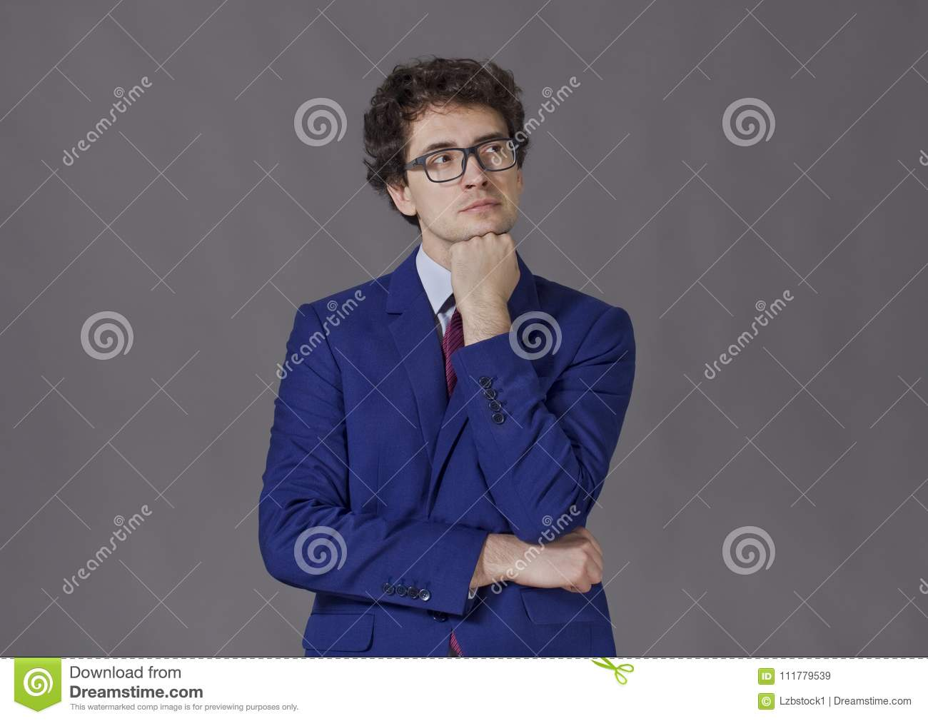Portrait of young businessman keeping fist to his beard