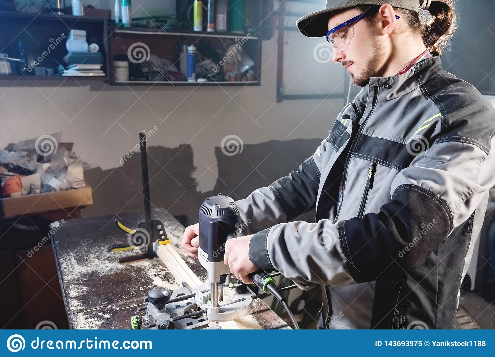 Portrait of a young carpenter joiner with electric milling cutter in the hands of a worker in a home workshop. Starting