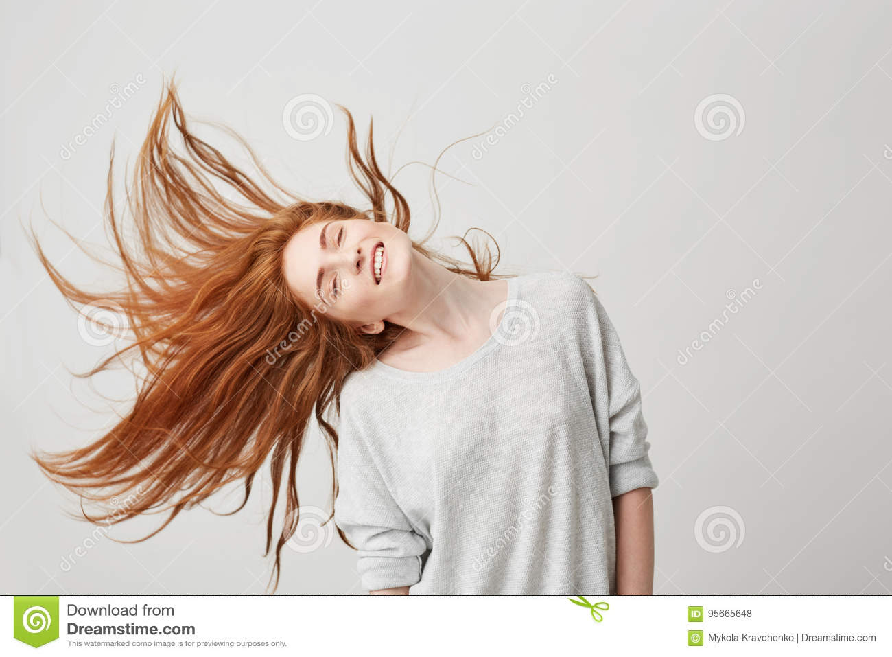 Portrait of young cheerful beautiful redhead girl smiling with closed eyes shaking head and hair over white background.