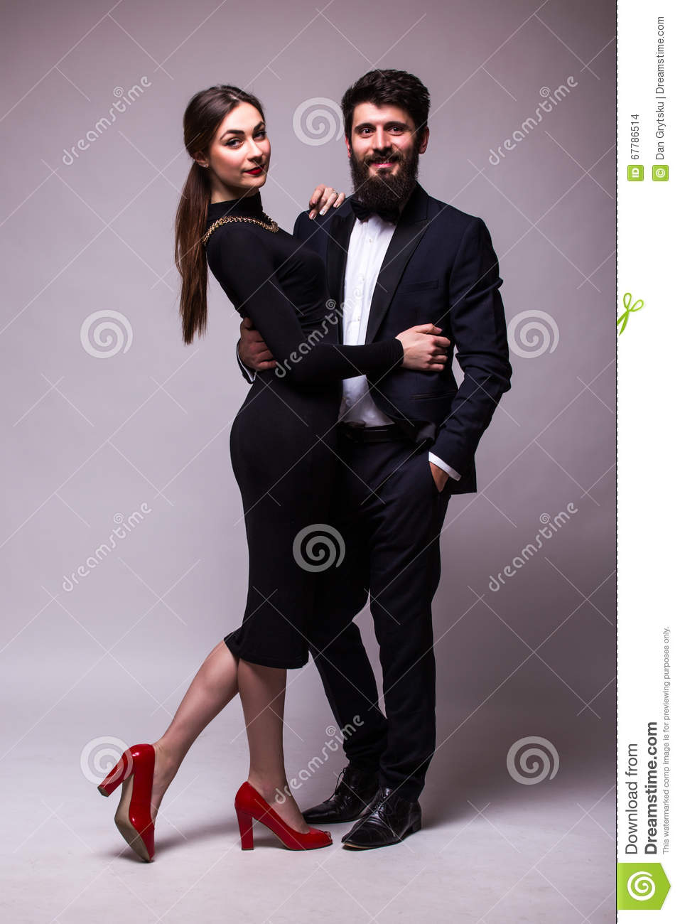 Portrait of young couple in love posing dressed in classic clothes on grey backround. Man with beard in Suit, Woman in black Dress