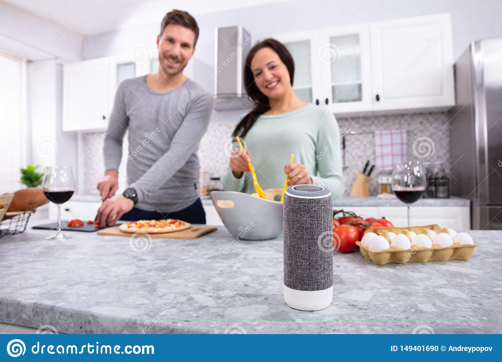 Portrait Of Young Couple Preparing Food In Kitchen
