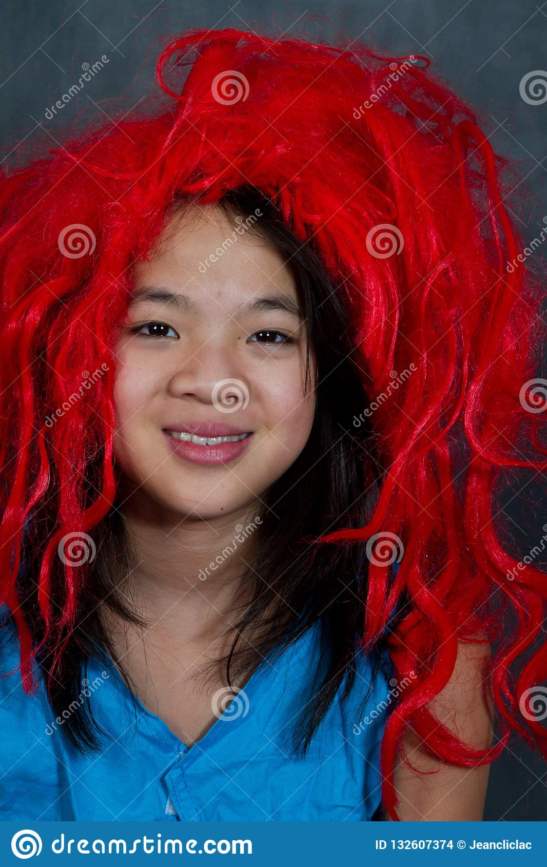 Portrait Of A Young Cute Girl With False Red Hair Looking At Th