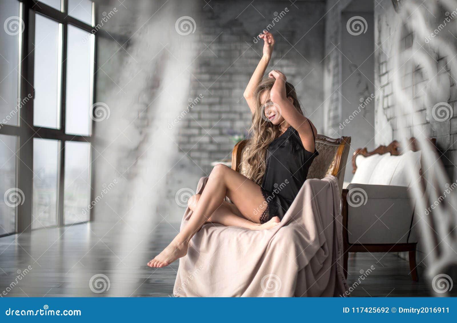 Portrait of young elegant woman. Fashion hairstyle, black short dress, armchair