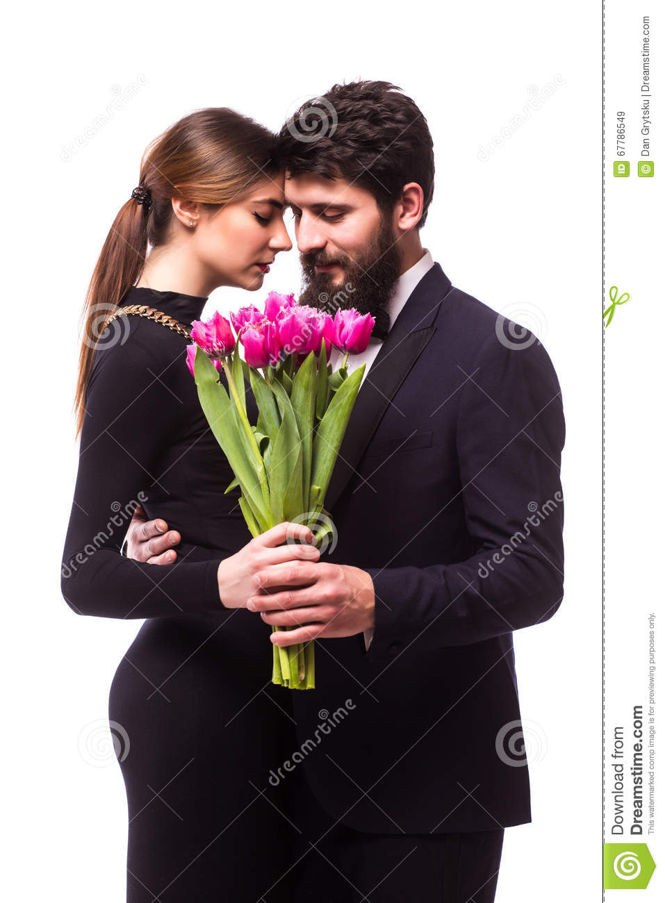 Portrait of young family couple in love with bouquet of lila tulips posing dressed in classic clothes on white backround.