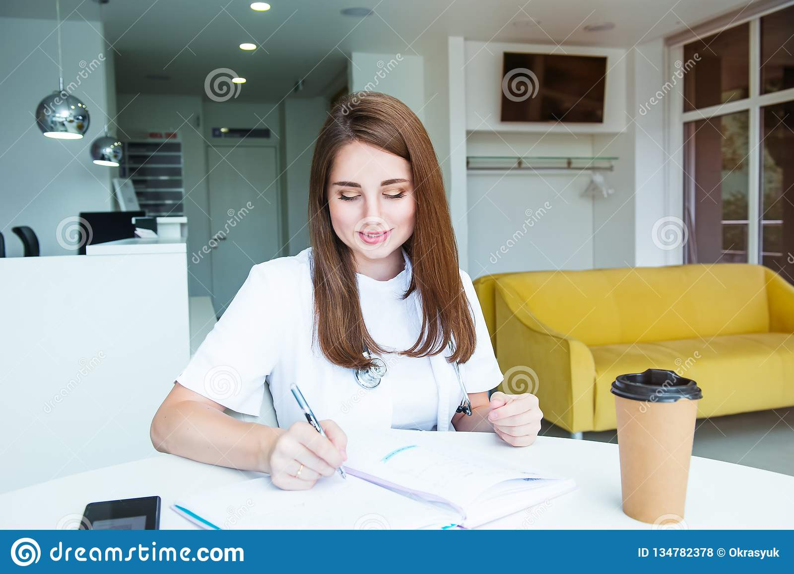 Portrait of young female doctor making notes in notebook while sitting behind the table with phone and coffee inside of medical