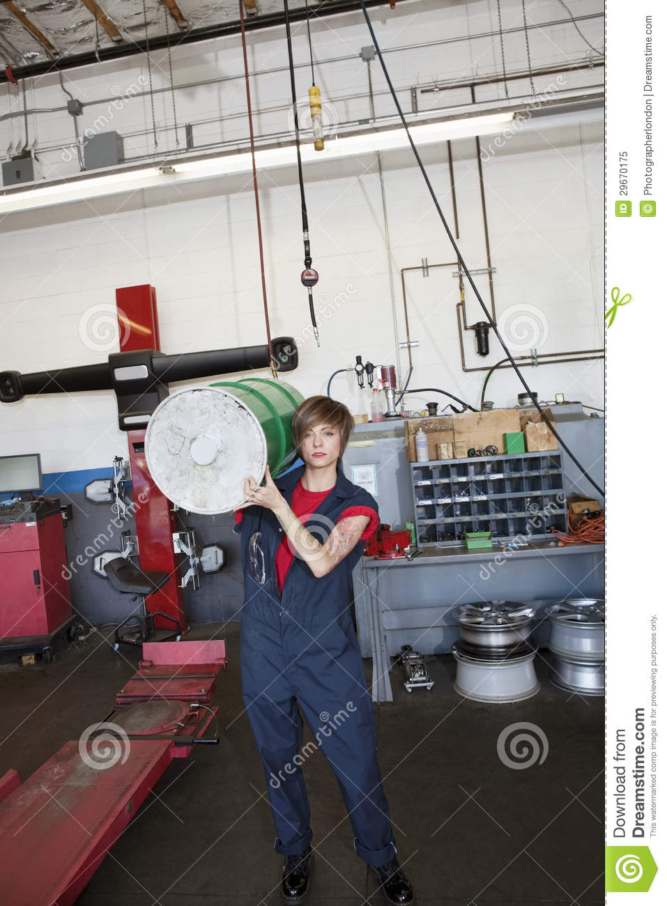 Portrait Of A Young Female Mechanic Carrying Oil Drum On
