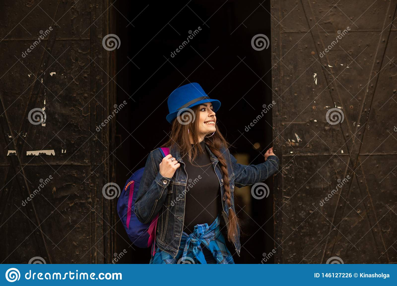 Portrait of a young girl on the background of the old black portal in the city of Lviv