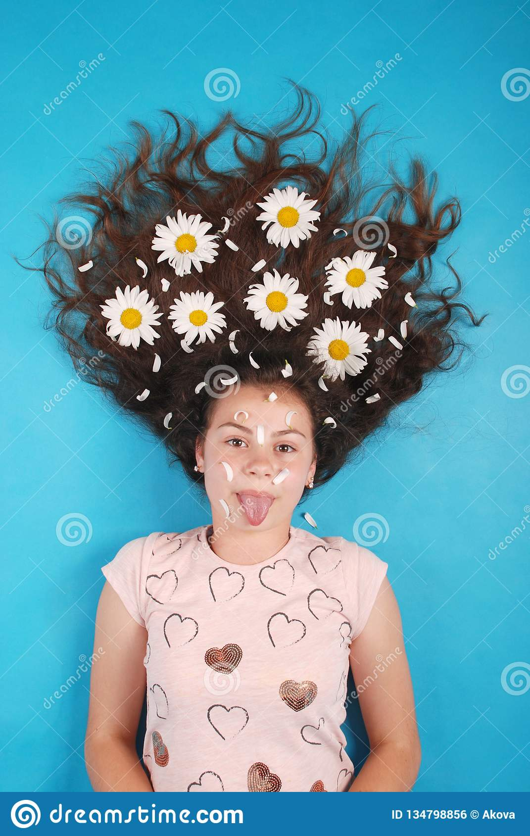 Portrait of a young girl with daisies in their hair lying on the floor