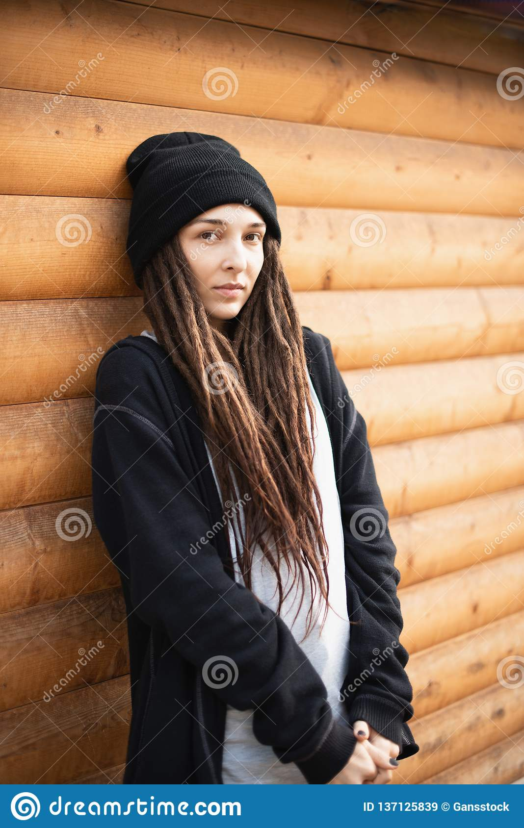 Portrait of a young girl with dreadlocks in a black hat and a black hoodie  on a wooden house background. sad beautiful girl. unusual hippie girl 981580da3aab